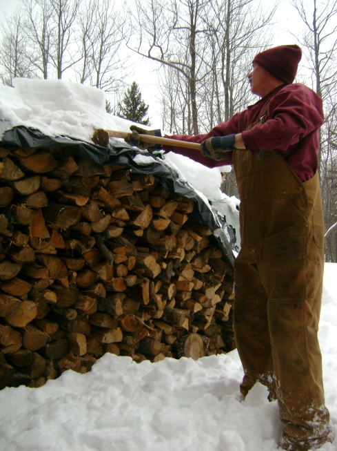Shoveling off the wood pile before hauling the logs inside