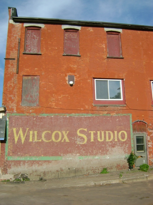 An old building and sign in Houghton advertising Wilcox Studio