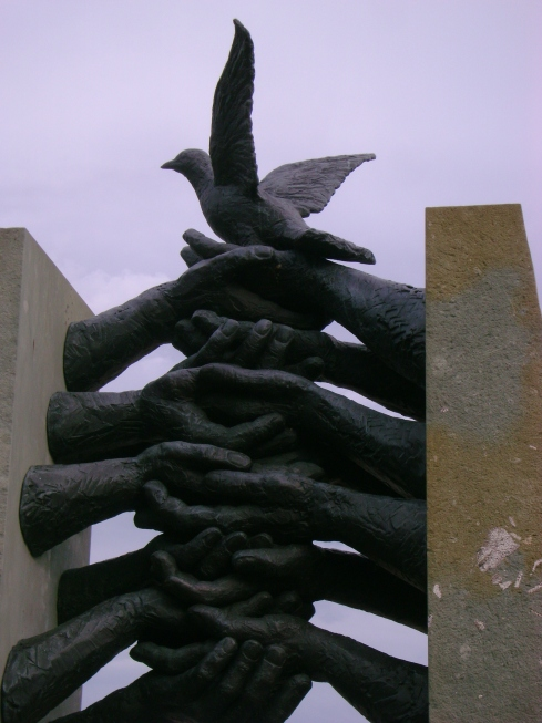 Statue of interlocking hands with bird of peace atop