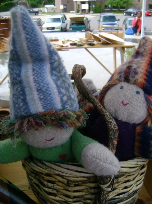 Homemade dolls peek out of their basket seeing if anyone will buy them.