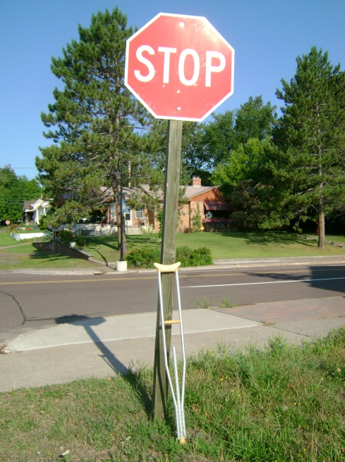 Why is there a crutch leaning against that stop sign and what does it mean...?