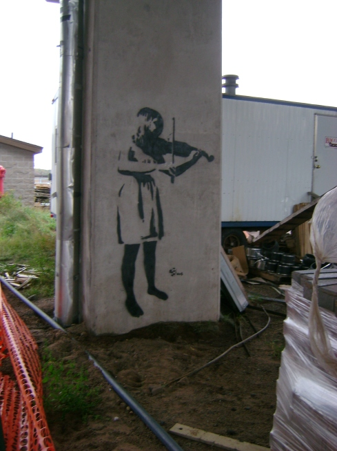 Girl playing violin in construction zone